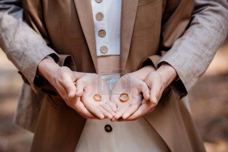 Foto de Vista recortada de pareja elegante sosteniendo anillos de boda - Imagen libre de derechos