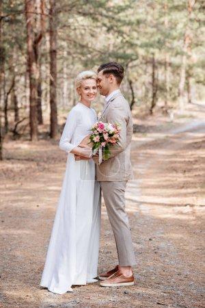 Photo pour Vue complète du couple marié embrassant dans la forêt - image libre de droit