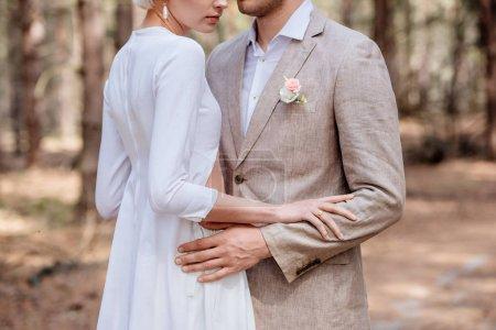 Photo pour Vue recadrée du couple marié embrassant dans la forêt - image libre de droit