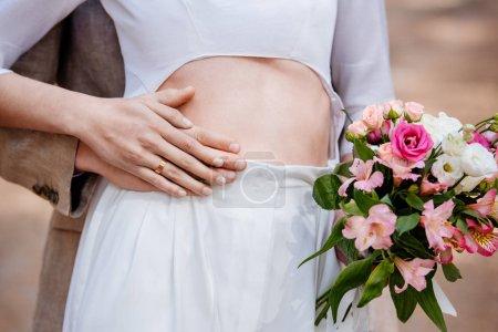 Photo pour Vue recadrée du marié embrassant la mariée avec bouquet de mariage - image libre de droit