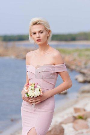 Photo pour Fille blonde pensive dans le bouquet rose de fixation de robe - image libre de droit