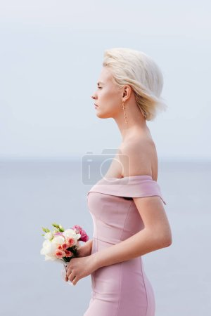 Photo for Side view of pensive blonde girl in pink dress holding bouquet - Royalty Free Image