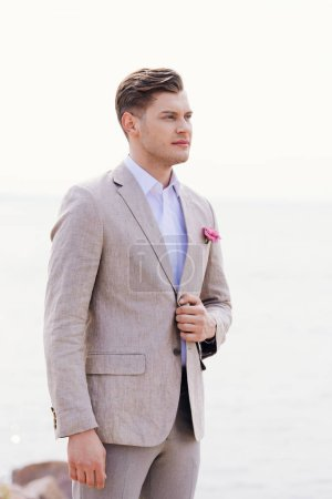 Photo for Dreamy bridegroom in formal wear with pink boutonniere looking away - Royalty Free Image