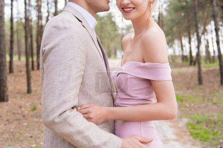 Photo pour Vue recadrée de heureux couple marié embrassant dans la forêt avec le sourire - image libre de droit