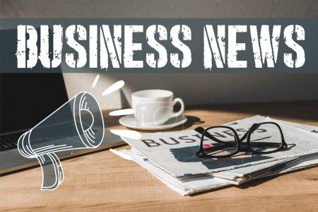 Photo pour Verres sur le journal d'affaires près de l'ordinateur portatif et de la tasse avec la soucoupe sur la table en bois avec des nouvelles d'affaires et l'illustration de haut-parleur - image libre de droit