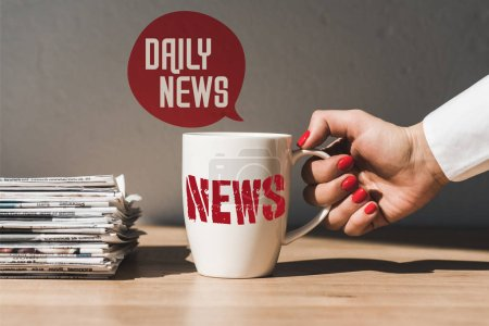 Photo for Cropped view of woman holding white cup with news lettering on wooden table near pile of different newspapers and speech bubble illustration with daily news text - Royalty Free Image