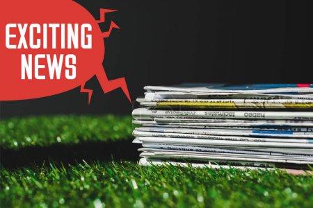 Foto de Pila de diferentes periódicos de impresión en hierba verde fresca cerca de la burbuja del habla roja con emocionantes letras de noticias aisladas en negro - Imagen libre de derechos
