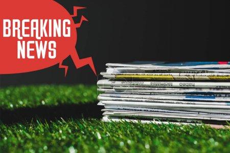 Foto de Pila de diferentes periódicos de impresión en hierba verde fresca cerca de la burbuja del habla roja con las letras de noticias de última hora aislada en negro - Imagen libre de derechos