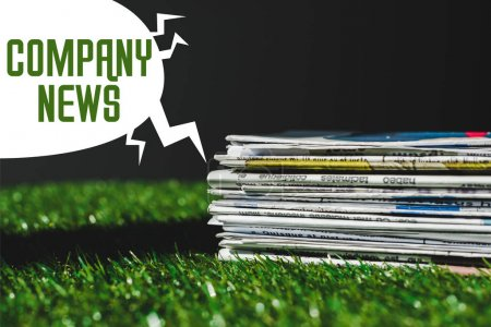 Photo pour Stack of different print newspapers on fresh green grass near speech bubble with company news lettering isolated on black - image libre de droit