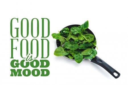 Photo pour Feuilles fraîches d'épinards dans la poêle sur le fond blanc près de la bonne nourriture est le lettrage vert de bonne humeur - image libre de droit