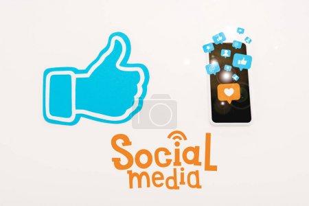 Photo pour Le pouce bleu vers le haut signent près du smartphone avec des icônes de médias sociaux d'isolement sur le blanc - image libre de droit