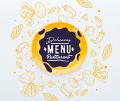 "Постер, картина, фотообои ""top view of shiny yellow plate with delicious restaurant menu lettering with vegetables illustration around on white background"""