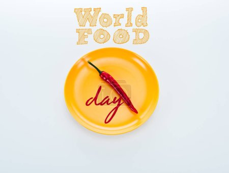 Photo pour Top view of red chili pepper on bright yellow plate with world food day lettering on white background - image libre de droit
