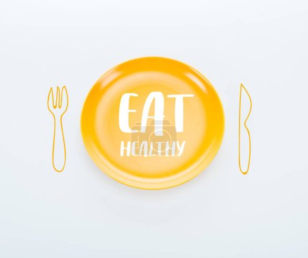 Photo for Top view of shiny yellow plate with eat healthy lettering and cutlery illustration on white background - Royalty Free Image