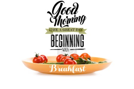 Photo for Cherry tomatoes with green spinach leaves in yellow plate with good morning, have a great day beginning with breakfast lettering above isolated on white - Royalty Free Image