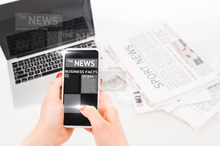 Photo for Selective focus of woman holding smartphone with business news illustration near laptop and newspapers - Royalty Free Image