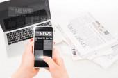 "Постер, картина, фотообои ""selective focus of woman holding smartphone with business news illustration near laptop and newspapers """