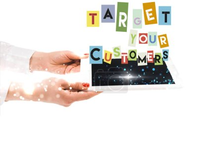 Photo for Cropped view of woman holding digital tablet with target your customers lettering isolated on white - Royalty Free Image