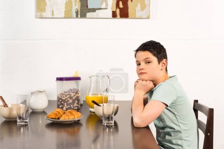 Foto de Preteen boy sitting at the table during breakfast and looking at camera - Imagen libre de derechos