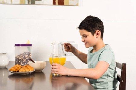 Photo pour Garçon de sourire retenant le verre et la cruche avec le jus d'orange dans la cuisine - image libre de droit