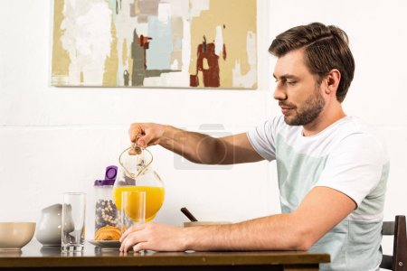 Photo for Man pouring orange juice in glass during breakfast in kitchen - Royalty Free Image