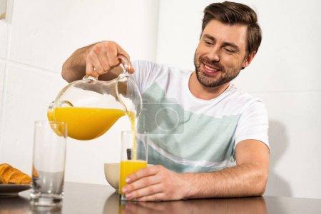 Foto de Smiling man pouring orange juice in glass during breakfast in kitchen - Imagen libre de derechos