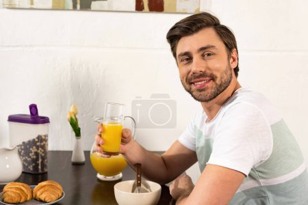 Photo for Smiling bearded man holding glass of orange juice during breakfast - Royalty Free Image