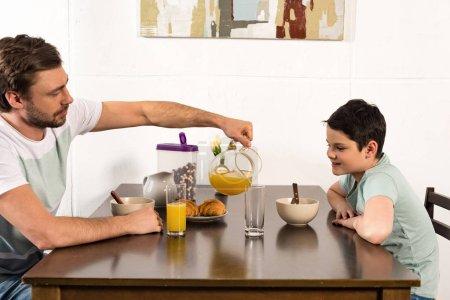 Photo pour Papa barbu versant le jus d'orange au fils pendant le petit déjeuner - image libre de droit