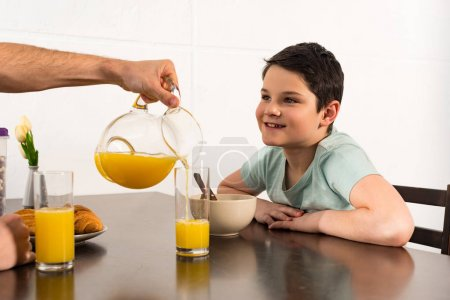 Photo for Cropped view of dad pouring orange juice to son during breakfast - Royalty Free Image