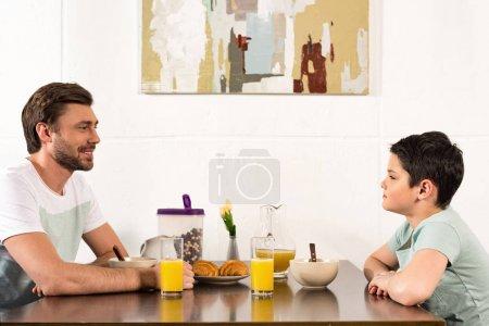 Foto de Padre sonriente e hijo mirándose durante el desayuno - Imagen libre de derechos