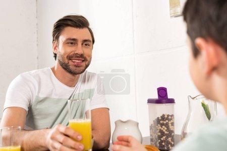 Photo pour Vue recadrée de fils et de papa souriant retenant le verre de jus d'orange pendant le petit déjeuner - image libre de droit