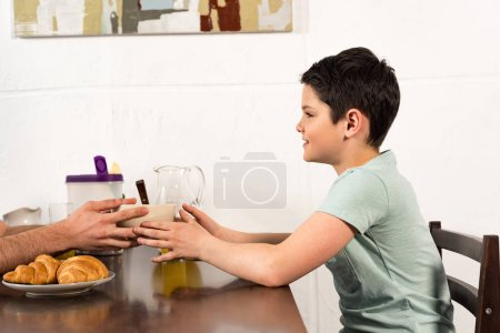 Photo for Cropped view of dad and son having breakfast together - Royalty Free Image