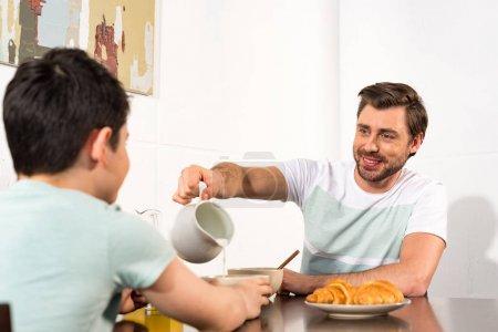 Photo pour Papa versant du lait dans un bol pendant le petit déjeuner avec son fils - image libre de droit