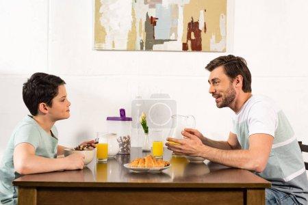 Foto de Padre e hijo sonrientes desayunando y mirándose en la cocina - Imagen libre de derechos