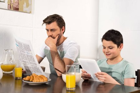 Photo for Pensive father reading newspaper and son using digital tablet during breakfast - Royalty Free Image
