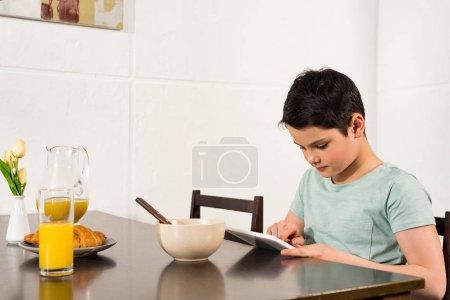 Photo pour Garçon utilisant la tablette numérique pendant le petit déjeuner dans la cuisine - image libre de droit