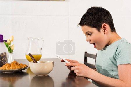 Photo pour Garçon choqué utilisant la tablette numérique pendant le petit déjeuner dans la cuisine - image libre de droit