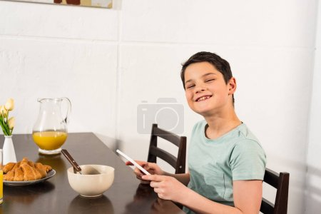 Photo for Smiling boy using digital tablet during breakfast in kitchen - Royalty Free Image