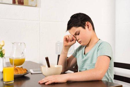 Photo pour Garçon triste s'asseyant à la table pendant le petit déjeuner dans la cuisine - image libre de droit