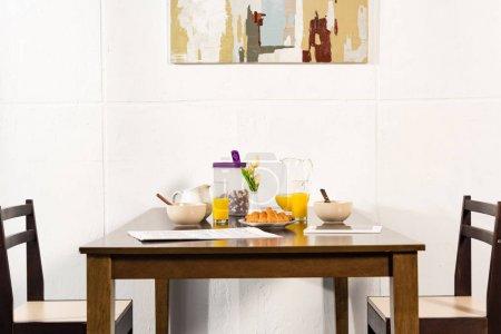 Photo pour Chaises et table avec jus d'orange, croissants et céréales de petit déjeuner dans la cuisine - image libre de droit