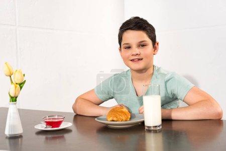 Photo pour Garçon de sourire s'asseyant à la table avec le croissant, le sirop et le verre du lait - image libre de droit