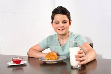 Photo for Smiling boy sitting at table with croissant, syrup and glass of milk - Royalty Free Image