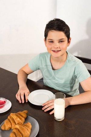 Photo pour Vue au-dessus du ciel du garçon souriant s'asseyant à la table avec des croissants, du sirop et du verre de lait - image libre de droit