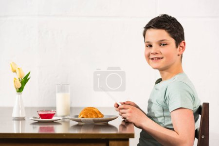smiling boy using digital tablet during breakfast in kitchen