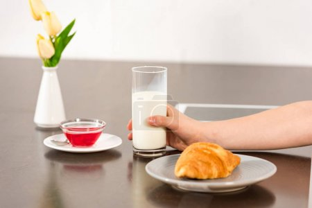 Photo for Cropped view of boy sitting at table with croissant, syrup and glass of milk - Royalty Free Image