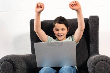Photo pour Garçon excité dans des jeans s'asseyant dans le fauteuil et utilisant l'ordinateur portatif - image libre de droit