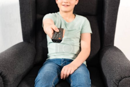 Photo for Boy in jeans sitting in armchair and holding remote controller - Royalty Free Image
