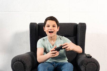 Photo pour Kiev, Ukraine - 17 avril 2019: garçon excité avec joystick assis dans un fauteuil et jouant à un jeu vidéo - image libre de droit