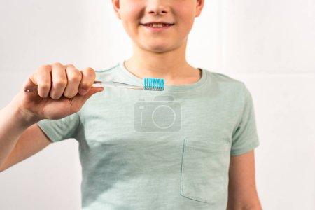 Photo pour Vue recadrée de garçon de sourire retenant la brosse à dents dans la salle de bains - image libre de droit