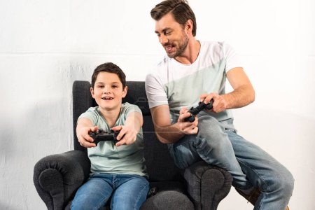 Photo for KYIV, UKRAINE - APRIL 17, 2019: smiling son and dad holding joysticks and playing video games together - Royalty Free Image